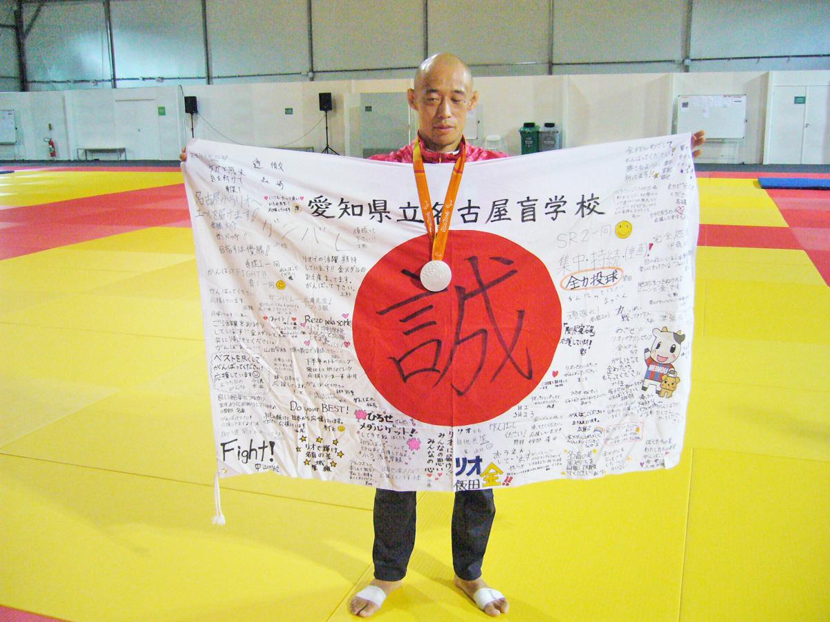 2016年リオにて。銀メダルを首からさげ、盲学校の応援幕を広げる廣瀬さん